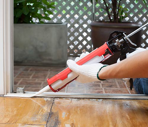 Homeowner caulking patio door